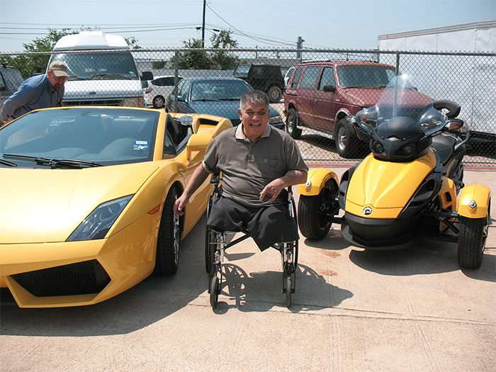 Man in wheelchair smiles in front of a Lamborghini and a Canam Spider.