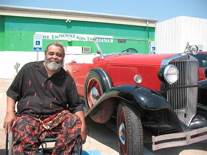 Smiling man in wheelchair in front of 1930's Hupmobile.