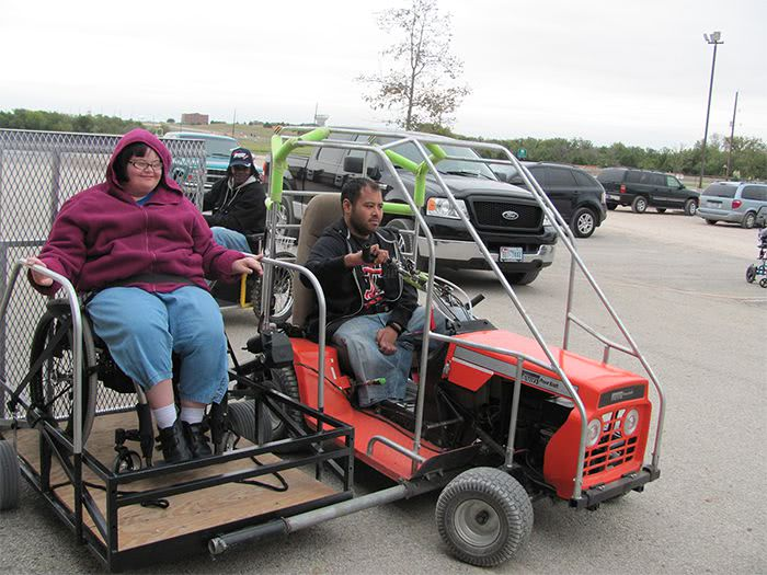 Chris gives a woman a ride on the Orange Mower Kart with Sidecar.