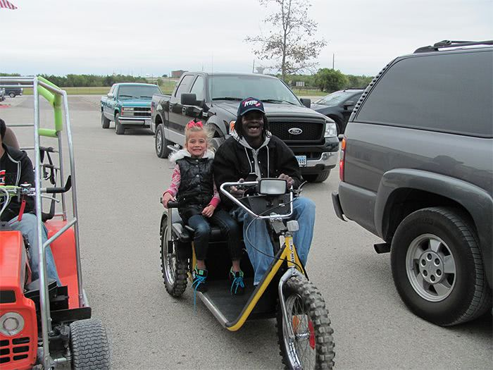 Tommie gives a young girl a ride on the Yellow Modified 3-Wheeler.