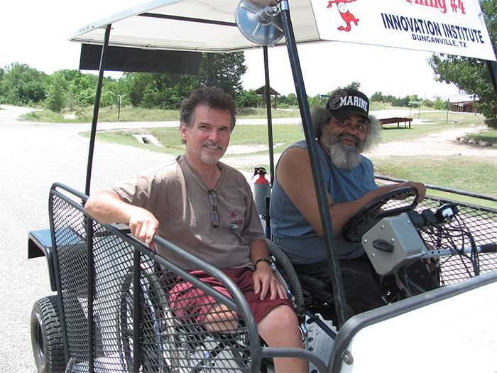 Wandus and a man smile during a ride on the White Hybrid Kart.