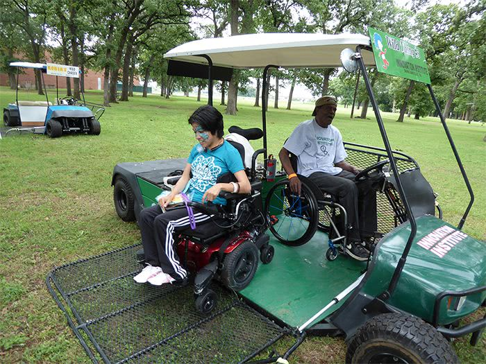 Young woman rolling her powerchair down the ramp of the Green Kart.
