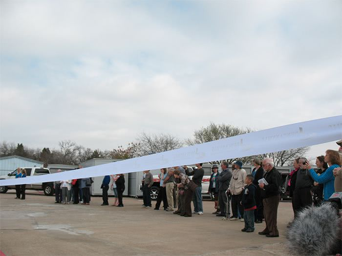 People standing behind a ribbon at the Grand Opening ceremony.