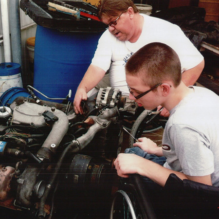 Tony teaches a young man automotive repair.