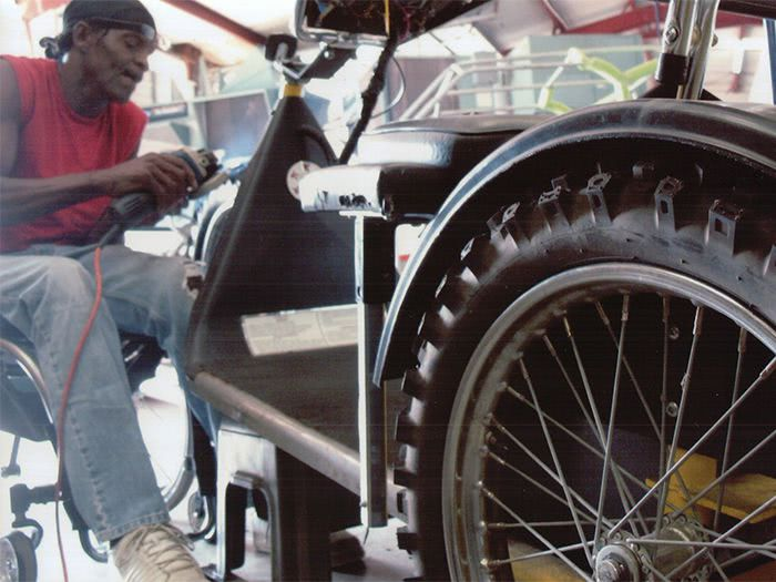 Tommie works on widening the front fork to accommodate the larger wheel.