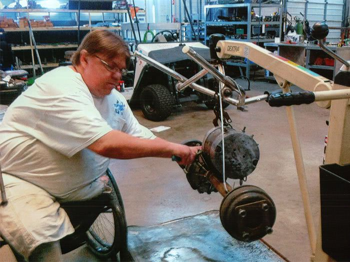 Tony works on the axle and motor for the White Hybrid Kart.